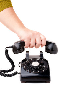 A hand  hanging up the handset of an old black vintage rotary style telephone isolated over white.