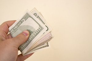A hand holding a big wod of cash isolated over a gold background.