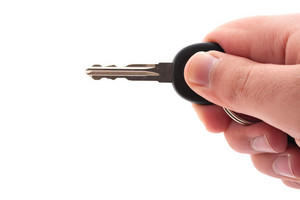 A hand holding a car or house key isolated over a white background.