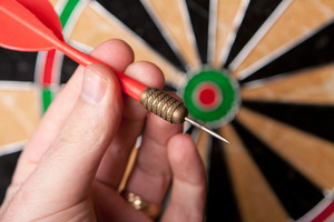 A hand holding a dart getting ready to aim at the dartboard. Shallow depth of field.