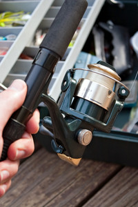 A hand holding a fishermans rod reel and tackle box ready for the start of fishing season.