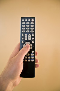 A hand holding a remote control isolated over a gold background.