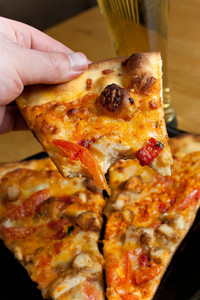 A hand holding a slice of buffalo chicken pizza from the first person point of view.  Shallow depth of field.