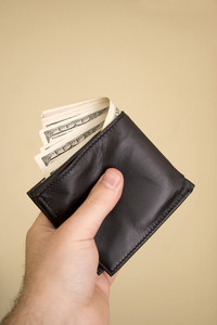 A hand holding a wallet full of cash isolated over a gold background