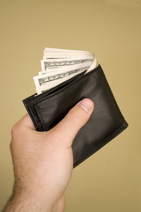 A hand holding a wallet full of cash isolated over a gold background.