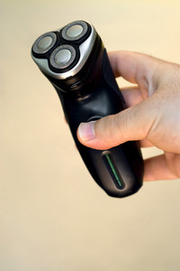 A hand holding an electric shaver isolated over a solid color background.  Shallow depth of field.