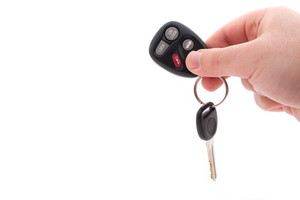 A hand holding car keys and a remote control for keyless entry isolated over white.
