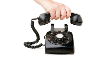 A hand  holding the handset of an old black vintage rotary style telephone isolated over white.
