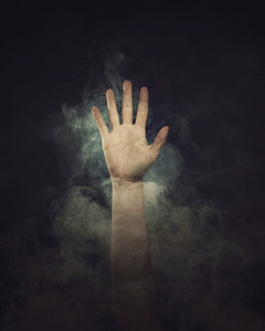 A hand reaches out in the black background from the smoke.