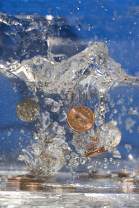 A handful of coins dropping into some water.