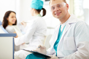 A handsome dentist smiling at camera with a nurse and a patient in the background