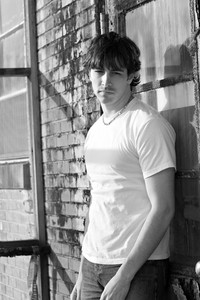 A handsome young man posing in a grungy urban setting.
