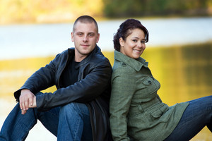 A happy interracial couple sitting outdoors by a lake or pond.