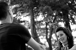 A happy young couple in their mid 20s smiling in black and white.