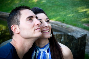 A happy young couple in their mid 20s smiling with their heads close together.