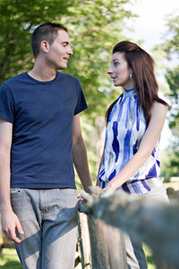 A happy young couple in their mid 20s talking to one another outdoors.