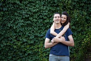 A happy young couple in their mid 20s together outdoors in front of some green ivy.
