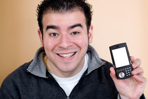 A happy young man showing the screen of a smartphone.  The white cell phone screen includes the clipping path.