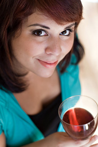 A happy young woman holding a glass of red wine.  Shallow depth of field with focus on the eyes.