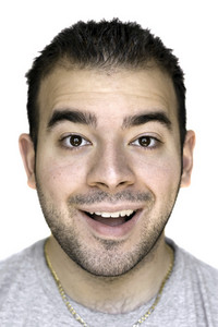 A headshot of a young man that is amazed or thrilled about something.