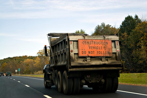 A heavy duty construction dump truck driving on the highway.