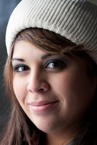 A Hispanic brunette woman with a friendly smile on her face wearing a knit cap on her head.