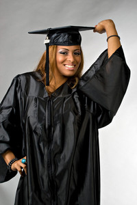 A hispanic girl at graduation posing in her cap and gown isolated over a silver background.