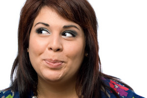A Hispanic woman isolated over white with a mischievous look on her face.