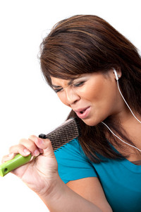 A Hispanic woman listening to music playing through her stereo earbud headphones and pretending to sing on a microphone that is actually a hair brush.