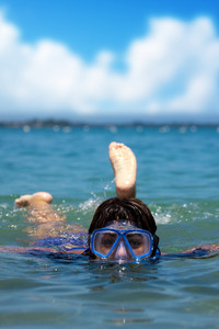 A Hispanic woman snorkeling in the tropical waters of the Caribbean sea.