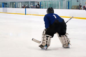A hockey goalie awaiting the return of the puck so he can resume his defensive role.  Shallow depth of field.