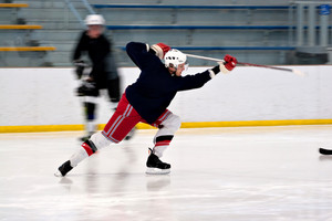 A hockey player shooting the puck as he speeds down the ice.  Slight motion blur.