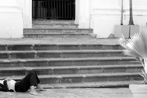 A homeless and destitute individual lays helplessly on the stone stairway in the city.