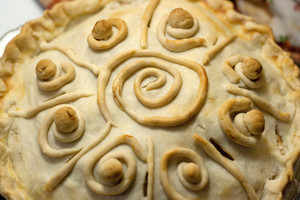 A homemade baked apple pie with custom swirl designs on the crust.