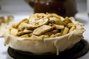 A homemade deep dish apple pie being prepared for baking before the top crust was added.