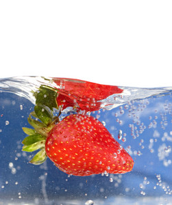 A juicy red strawberry plunging into some water. Shallow depth of field.