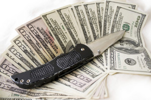 A knife and some fanned out cash laying on a bed.  This works for all sorts of illegal activities such as prostitution, drug dealing, and gang activity.