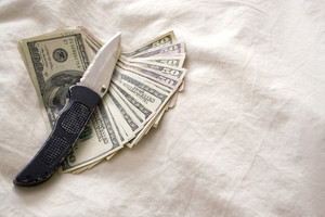 A knife and some fanned out cash laying on a bed.
