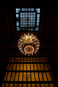 A large hanging chandelier inside the New York Grand Central Terminal train station.