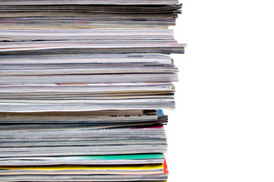 A large pile of magazines stacked high. Isolated over white with copyspace.