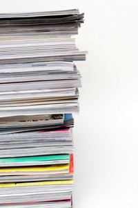 A large stack of magazines piled high.  Isolated over white with copyspace.