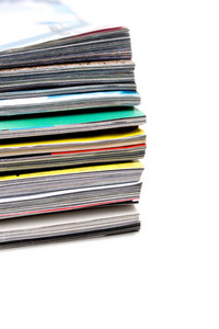 A large stack of old magazines piled high.  Isolated over white with copyspace.