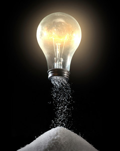 A light bulb with salt pouring out of the bottom.