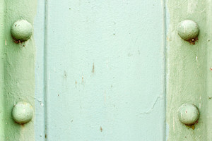 A light green painted metal background texture with four rusted bolts or rivets.