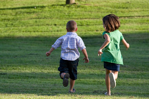A little boy and girl run through the grassy field without a care in the world.