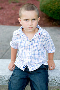 A little boy with a serious or bored expression on his face.
