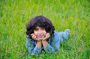 A little cute happy girl laying on green ground