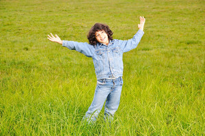 A little cute happy girl standing on green ground
