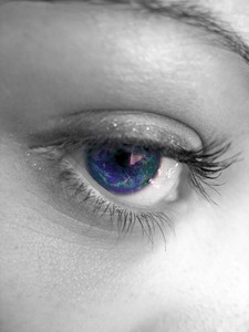 A macro shot of a pretty woman's eye with selective color.  An image of the earth is superimposed inside the eye.