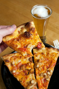 A male hand feeding himself buffalo chicken pizza from the first person point of view.  Shallow depth of field.